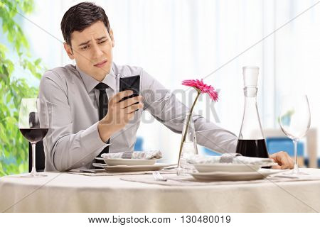Disappointed young man sitting at a restaurant table and reading a text message on his cell