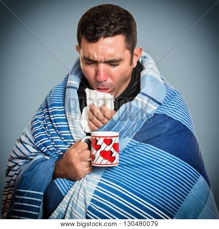 Portrait of a sick man with the flu coughing and holding a warm tea cup