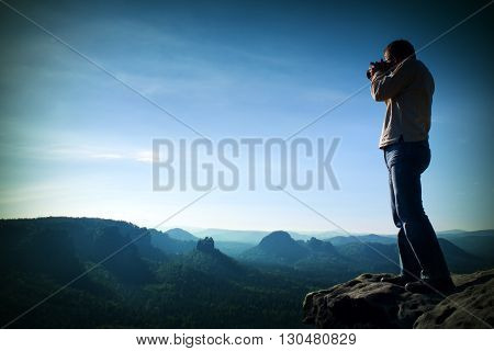 Professional photographer takes photos with big camera on peak of rock. Dreamy misty landscape hot Sun above