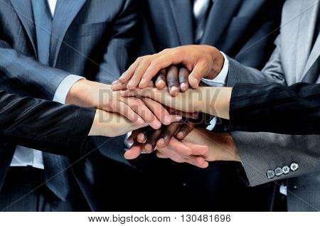 group of workers with their hands together in form of teamwork