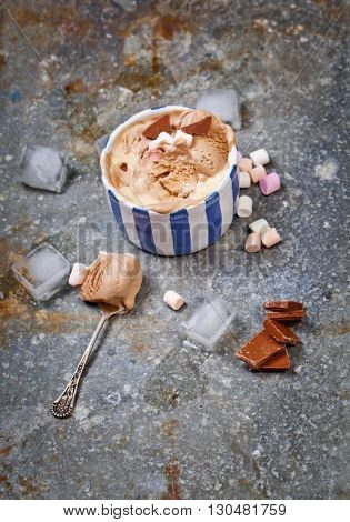 Homemade vanilla and chocolate ice cream with marshmallow, served in ceramic bowl over gray metal textured background.