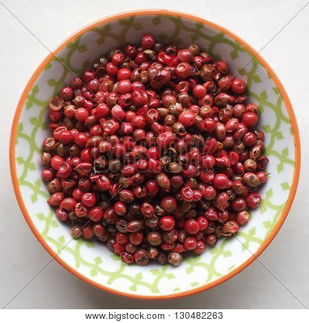 Bright red dried peppercorns in a small colorful ceramic bowl.