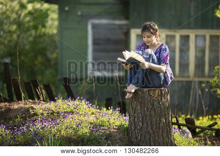 Teen girl reads book sitting on a stump in the yard of a country house.