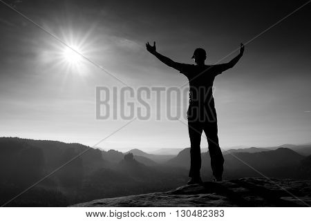 Happy Man Gesture In Red Cap Of Triumph With Hands In The Air. Funny Hiker On The Peak Of Sandstone