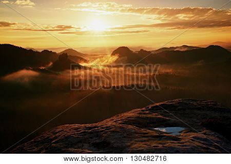 View Over Wet Sandstone Cliff Into  Heavy Misty Valley In Saxony Switzerland. Peaks Of Hills Increas