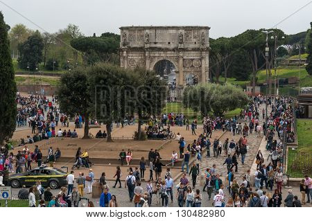 ROME ITALY - APRIL 7: Tourists visiting Arco de Constantino (Arch of Constantine) and Colosseum. The arch was erected by the Roman Senate to commemorate Constantine victory over Maxentius