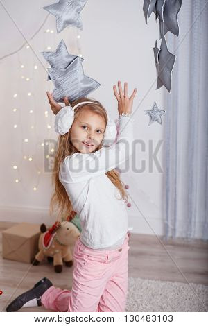 Portrait Of A Beautiful Little Girl In A In Earmuffs In The Interior With Christmas Decorations.