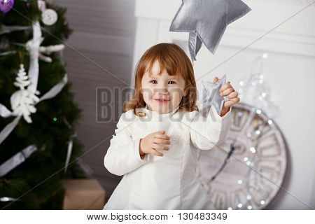 Portrait Of A Beautiful Little Girl In A White Dress In The Interior With Christmas Decorations