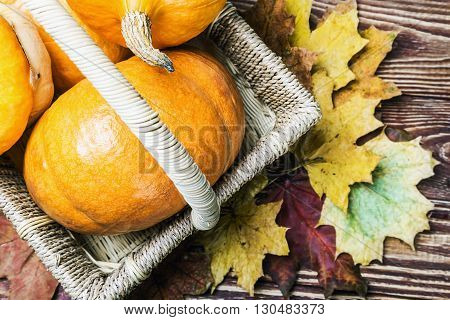 pumpkins for Halloween in a basket on a wooden table. Focus on pumpkins