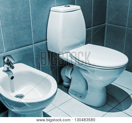 white ceramic toilet in tiled bathroom. Focus on the edge of the toilet bowl. toned image