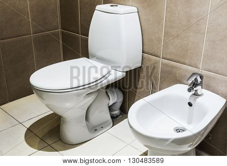 white ceramic toilet in tiled bathroom closet