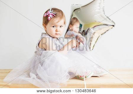 Little Baby Girl Holding Silver Star-shaped Balloon.