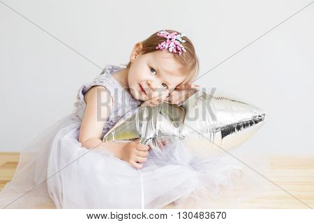 Portrait Of A Lovely Baby Girl Playing With Silver Star-shaped Balloon.
