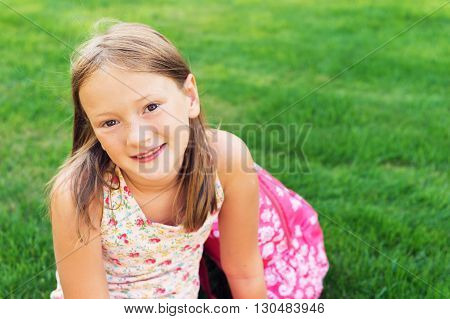 Cute young girl resting after school, sitting on bright green lawn, back to school concept