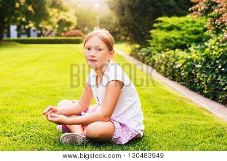 Outdoor portrait of a cute little kid girl of 7-8 years old, sitting on bright green lawn at sunset. Child playing on backyard in the evening