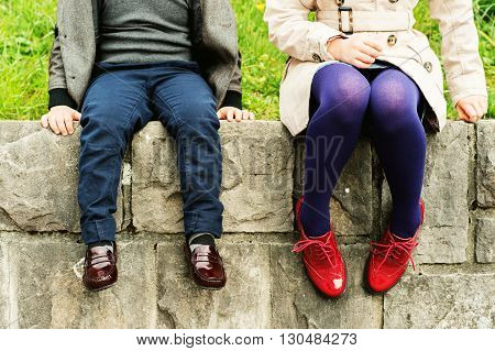 Two pairs of kids feet wearing fashion shoes, little boy wearing blue trousers and brown moccasins, schoolgirl in trench coat, purple tights and red brogues