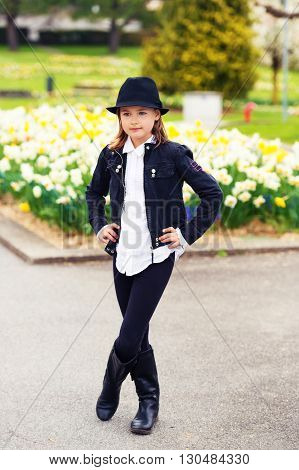 Cute little girl of 7-8 years old playing in the spring park, wearing black stylish set of black jacket, leggings, hat, boots and white blouse