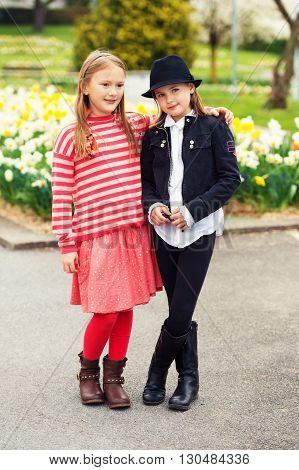 Outdoor portrait of two adorable fashion little girls