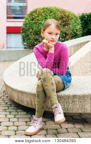 Fashion portrait of a cute little girl in a city, wearing pink shoes, t-shirt, denim skirt and green tights