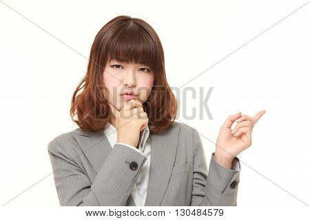 portrait of young Japanese businesswoman doubting on white background