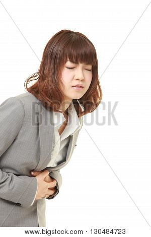 portrait of young Japanese businesswoman suffers from stomachache on white background