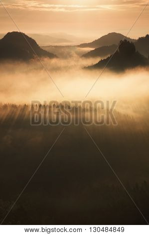 Distant Mountain Range And Heavy Clouds Of Colorful  Mist Above Deep Valleys