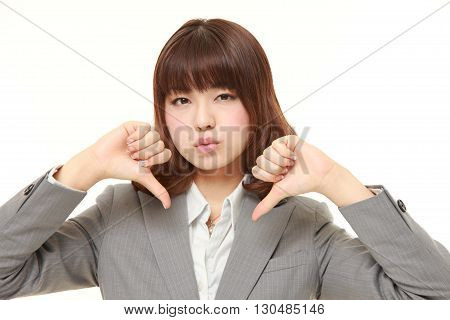 portrait of young Japanese businesswoman with thumbs down gesture on white background
