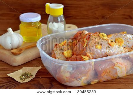 Raw chicken drumsticks with spices, olive oil, garlic, salt prepared for frying. Ingredients for cooking meat. Uncooked chicken legs. Plastic container with chicken legs