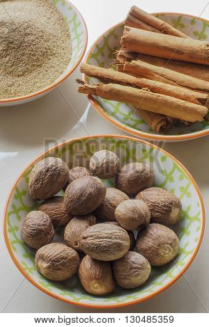 An assortment of spices in colorful ceramic bowls - whole nutmegs, cinnamon sticks and ground cardamom.