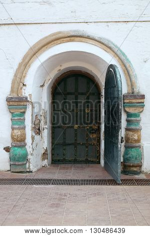 Wooden door and a fragment of a wall with an ornament. Texture background
