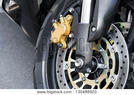 Close up view on braking mechanism on clean new motorcycle wheel with large bolts and chrome parts