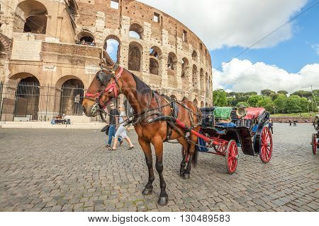 Rome, Italy - May 12, 2016: Typical horse-drawn carriage with tourists in front of Colosseo, Colosseum, Flavian Amphitheatre,  the largest amphitheater in the world and one of the symbols of Italy.