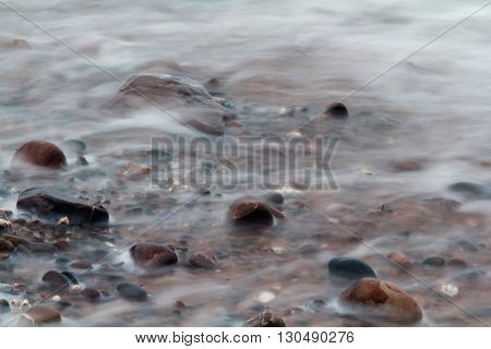 Waves Over Pebbles On Beach. Long Exposure.