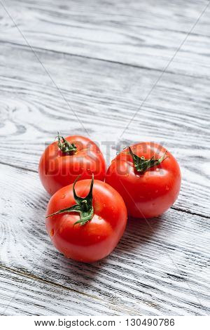 Three red tomatoes on a wooden background