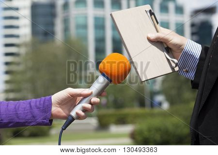 Media interview with microphone held in front of businessman or politician