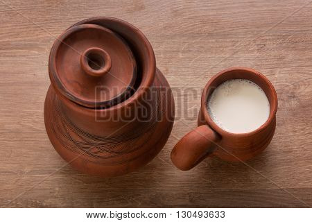 Top view of clay jug and mug with milk on the wooden table