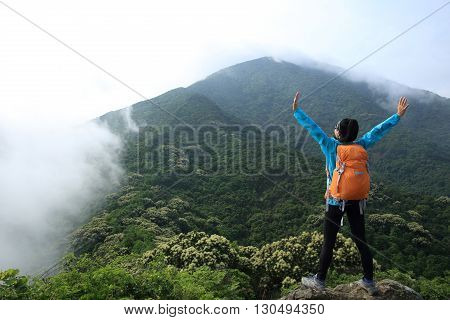 cheering young woman enjoy the view on mountain peak