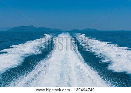 Waves on blue sea behind the speed boat with mountain and sky so blue on the background.