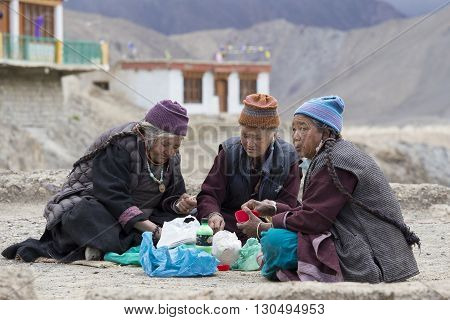 LAMAYURU INDIA - JUNE 14 2015: Unidentified buddhist old women during mystical mask dancing Tsam mystery dance in time of Yuru Kabgyat Buddhist festival at Lamayuru Gompa Ladakh North India