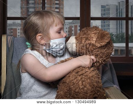 Little kid in a medical mask kissing toy bear. The house, the windows of houses, gray, dirty city. Conceptually about diseases, infections and allergies. Smog in the city, ecology