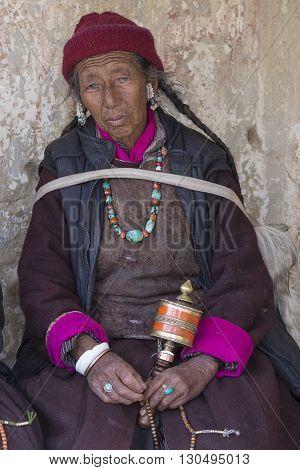 LAMAYURU INDIA - JUNE 15 2015: Unidentified buddhist old woman during mystical mask dancing Tsam mystery dance in time of Yuru Kabgyat Buddhist festival at Lamayuru Gompa Ladakh North India