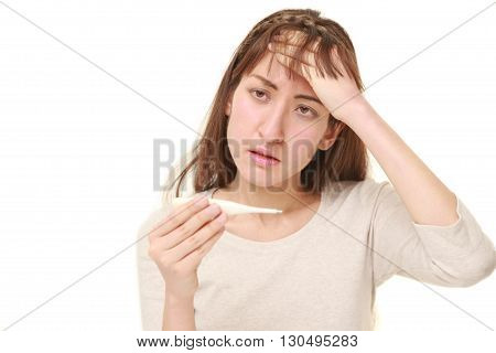 portrait of young woman with fever on white background