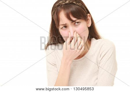 portrait of woman holding her nose because of a bad smell on white background