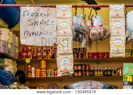 London United Kingdom - May 14 2016: Brixton Village and Brixton Station Road Market. Colorful and multicultural community market run by local traders in South London. Frozen snails available sign