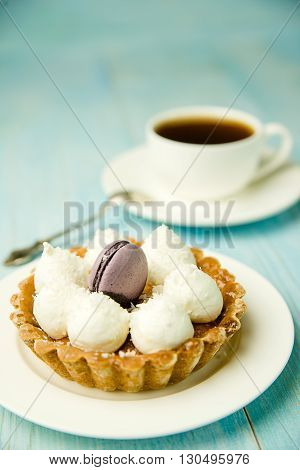 Cake with cream and white cup on the table