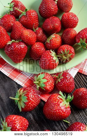 Strawberries in a plate on a green towel