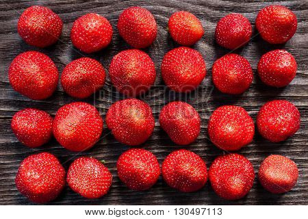 Strawberries laid out in rows on the wooden table