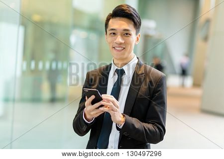 Businessman sending sms on mobile phone