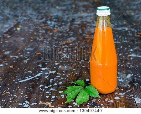 Bottled orange carrot juice on wooden background