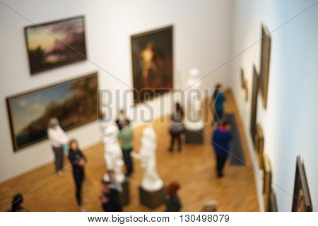 People visiting art gallery or museum and watching paintings and sculptures from top view blurred image